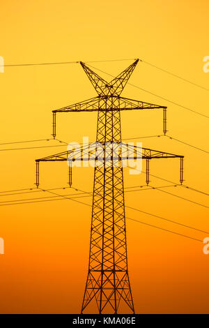 High-voltage electricity pylon / transmission tower silhouetted against sunset - Stock Photo