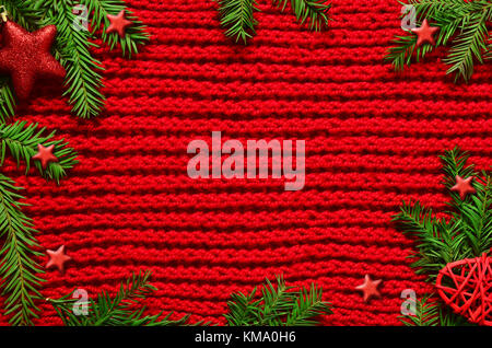 Christmas red knitted background with branch fir, stars, new year concept - Stock Photo