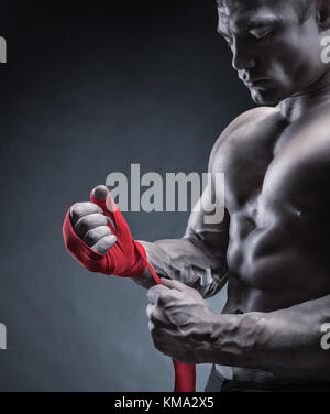 Close-up of a strong boxer putting on red straps and getting ready to fight - Stock Photo
