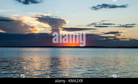 A spectacular inspirational brightly coloured cloudy sea water panoramic seascape landscape featuring crimson sun - Stock Photo