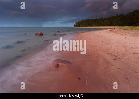 Sunset through the rain, Baltic sea coast at Kõpu peninsula, Hiiumaa island, Estonia, Europe - Stock Photo