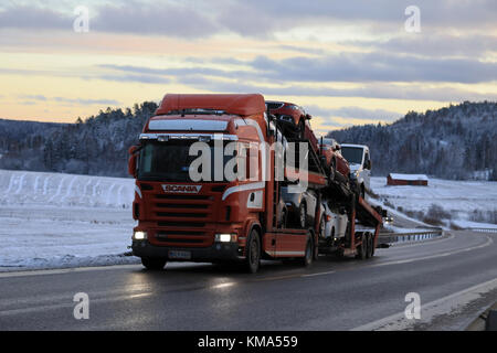SALO, FINLAND - DECEMBER 2, 2017: Red Scania R480 car carrier hauls new car at dusk along highway in winter. - Stock Photo