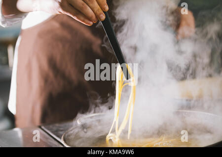 Chef cooking spaghetti in restaurant - Stock Photo