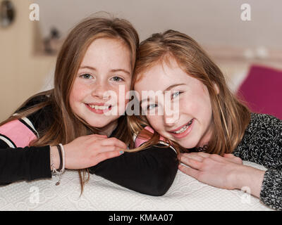 Two smiling young girls posing for the camera as a best friends forever concept. - Stock Photo
