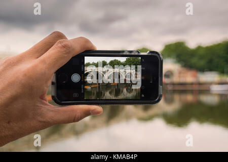 A male taking photos of Richmond Lock and Footbridge over River Thames with iPhone SE, Richmond, London - Stock Photo