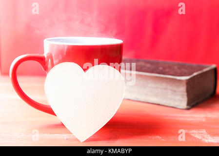 Greeting card idea with a red cup of hot drink with steam, a blank heart-shaped paper note leaned against it and - Stock Photo