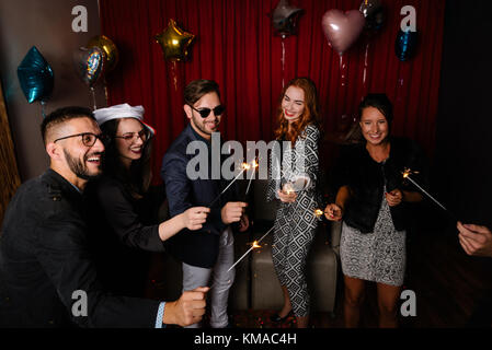 Group of people at a party playing with sparklers - Stock Photo
