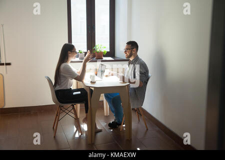 Coworkers sitting at meeting and discussing new concept in work. Two smiling millennial employees talking about - Stock Photo