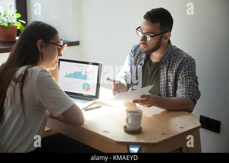 Two millennial coworkers having argument and business dispute in office. Businessman showing businesswoman paper - Stock Photo
