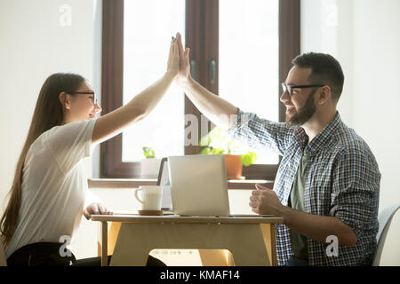 Teamwork concept: businessman and businesswoman giving high five and congratulating each other on success in teamwork. Millennial coworkers celebratin