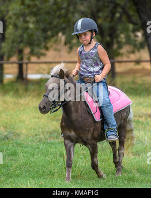 Four year old girl riding pony. - Stock Photo