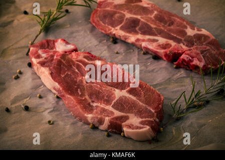 Horizontal photo of two slices of pork neck steaks. The meat portions with red color and fat is placed on worn baking - Stock Photo