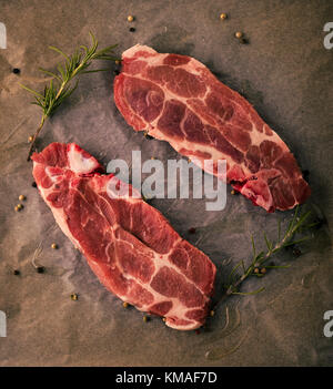 Vertical photo of two slices of pork neck steaks. The meat portions with red color and fat is placed on worn baking - Stock Photo