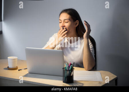 Exhausted millennial businesswoman in casual wear yawning at workplace in home office. Fatigued young female employer - Stock Photo
