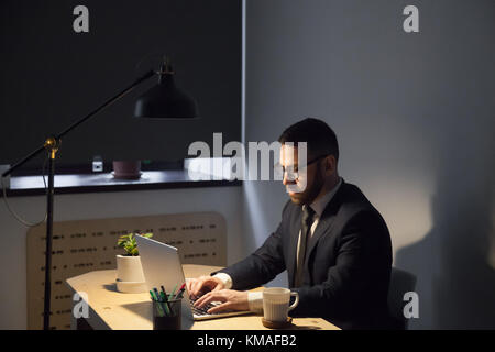 Millennial bearded employer in glasses typing on computer at night corporate shift. Confident male manager wearing - Stock Photo