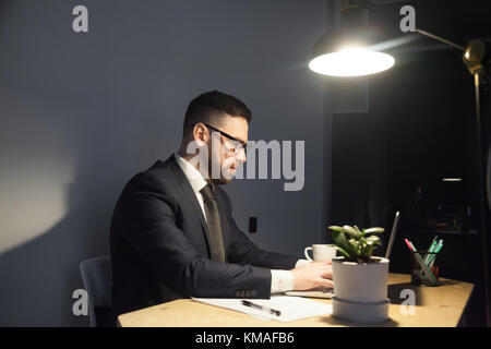 Young bearded male worker in suit and tie typing on laptop under light of lamp. Confident modern manager trying - Stock Photo