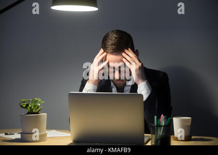 Portrait of tired anxious male worker with headache. Stressed man in glasses holding head in hands, looking at laptop - Stock Photo