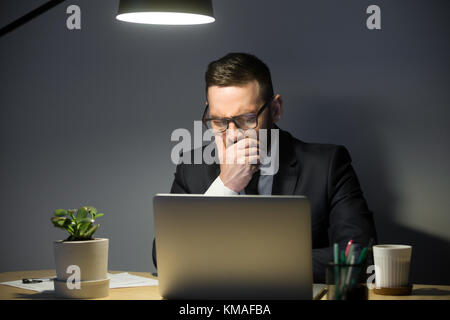 Concentrated male manager in glasses sitting in desk in office at night and analyzing market. Solution of hard business - Stock Photo