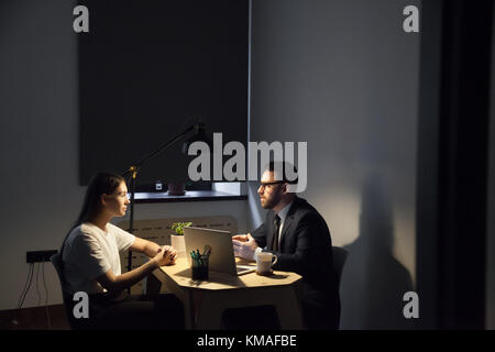 Coworkers sitting at desktop and discussing new concept in work. Two millennial employees talking about business - Stock Photo