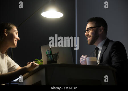 Millennial businesspeople have meeting in office at night. Happy smiling coworkers sitting at desktop and discussing - Stock Photo