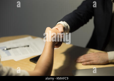 Businessman in suit greeting female coworker over desk in office after negotiations. Businesspeople reaching an - Stock Photo
