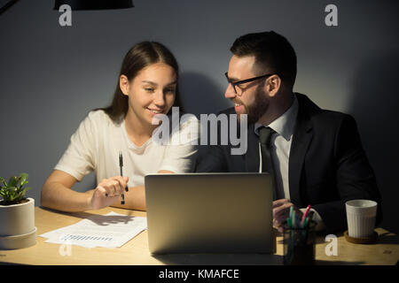 Attractive millennial businesswoman looking on laptop and smiling. Young bearded businessman in glasses and suit - Stock Photo