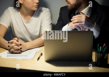 Bearded businessman in suit explaining new working project to female coworker. Businessman and businesswoman sitting - Stock Photo