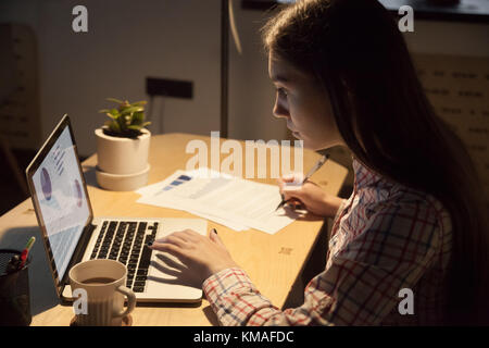 Young serious businesswoman in casual shirt checking work data on laptop and signing signature on business document. - Stock Photo