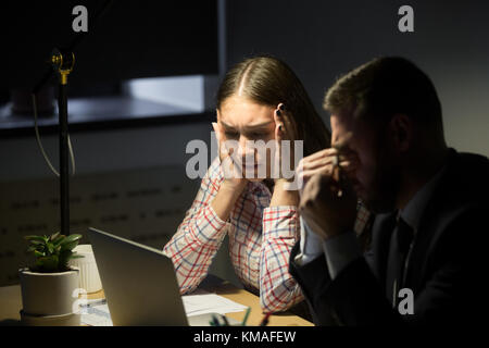 Depressed unhappy businessman and businesswoman having night shift in office and worried about work problem. Overwork, - Stock Photo