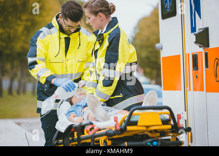 Emergency doctor giving oxygen to accident victim - Stock Photo