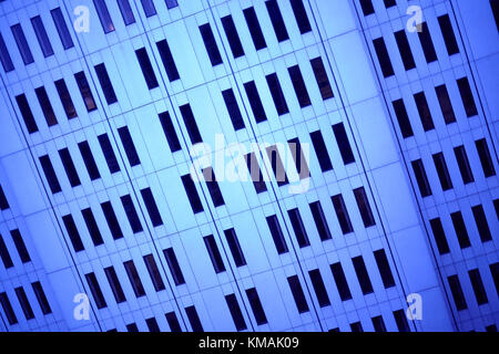 Full frame oblique view of the blue facade of a modern office building or skyscraper with symmetric architecture - Stock Photo