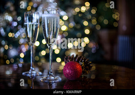 Two Champagne Glasses surrounded by Christmas Decorations - Stock Photo