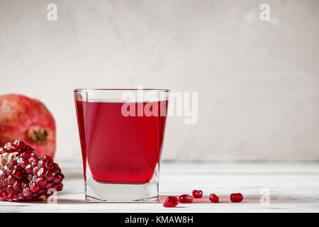 A glass of pomegranate juice with fresh pomegranate fruit and seeds scattered on wooden table. Healthy drink concept. - Stock Photo