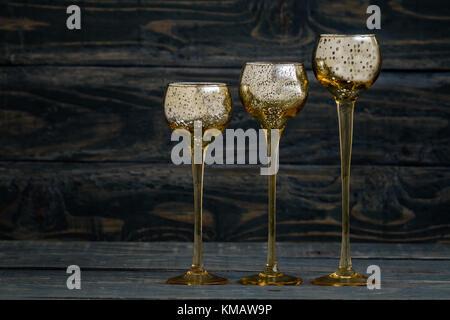 Yellow candle holders like wineglasses on blue background. - Stock Photo