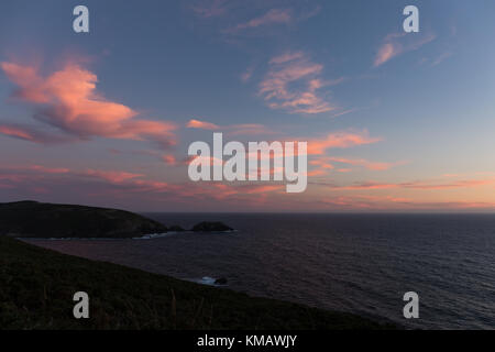 Sunset with red clouds in Ons Island, Atlantic Islands National Park, Pontevedra, Galicia, Spain - Stock Photo