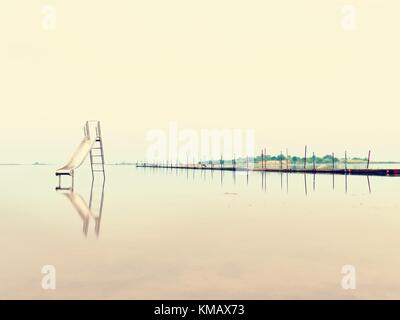 Sunset shore and old steel slide in lake. Chrome ladder tower with  sliding track, big granite stones around. Cold - Stock Photo
