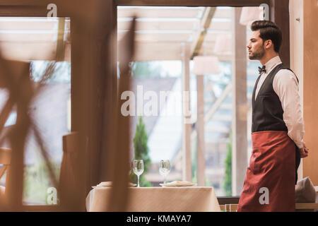 waiter standing near empty table - Stock Photo