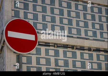 red stop sign on a tiled patterned wall - Stock Photo