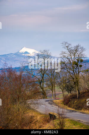 asphalt road turnaround through forested hills in springtime. high snowy peak of mountain ridge is seen in the distance - Stock Photo