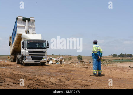 Worker watching a truck in a landfill area - Stock Photo