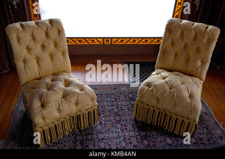 A pair of chairs framed by a window made by placing a filigree pattern cut out of black paper between sheets of - Stock Photo