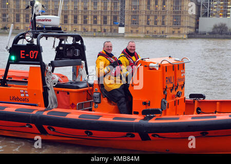 two of the volunteer crew on the Thames lifeboat in London sitting in the boat with the houses of parliament in - Stock Photo