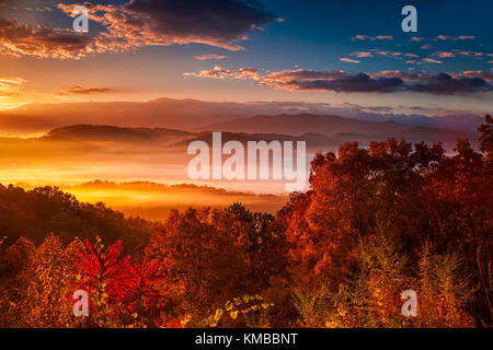 Colors of a brilliant sunrise over the mist shrouded mountains and ridges of the Great Smoky Mountain as seen from - Stock Photo
