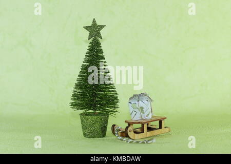 a miniature wooden sledge carrying a small gift next to a bright green Christmas tree on a light green background - Stock Photo