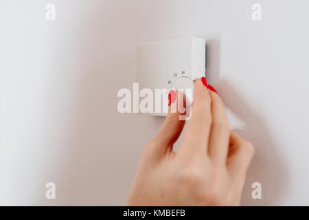 Woman regulating temperature on home heating thermostat on the wall - Stock Photo