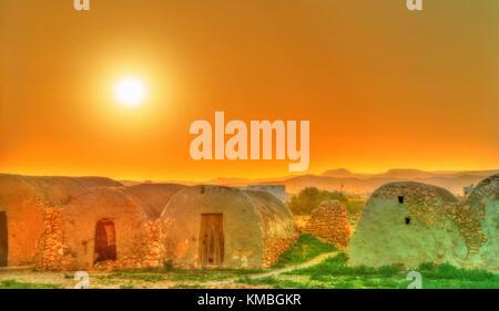 Sunset above Ksar Ouled Boubaker in Tunisia - Stock Photo