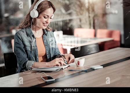 Smiling young woman having a productive morning in a cafe - Stock Photo