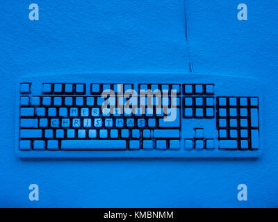 computer keyboard covered with snow illuminated by blue neon light with inscription merry christmas - Stock Photo