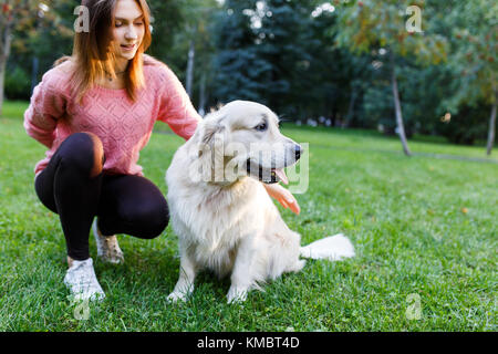 Photo of brunette with labrador lying on lawn in summer park - Stock Photo