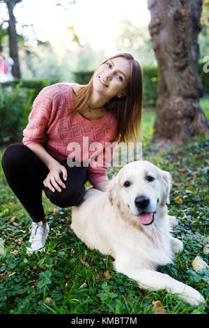 Picture of woman hugging dog on lawn - Stock Photo